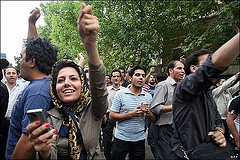 Protester in Iran. Note the woman holding a cell phone in the foreground.
